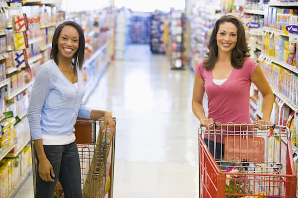 Two woman meeting in supermarket grocery ailse